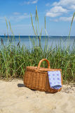 Picnic basket with blue white napkin on the beach. Picnic basket with blue white checkered napkin on sandy beach. Blurred seascape on the background Stock Images