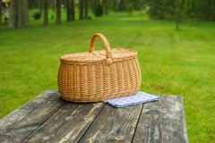 Picnic basket with blue white tablecloth on table. Picnic basket with blue white checkered tablecloth on wooden table. Summertime park lawn in the background Royalty Free Stock Photo