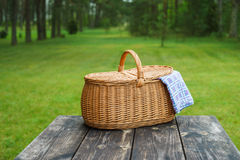 Picnic basket with blue white tablecloth on table Royalty Free Stock Photography