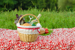 Picnic basket with a bottle of white wine, corkscrew, buns and bunch of basil on red tablecloth, plate with salad, tomat. Decorated picnic basket with a bottle Stock Images