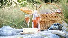 Picnic basket and bottle of wine on a grass