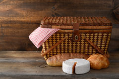 Picnic basket with bread and cheese on wood Stock Image