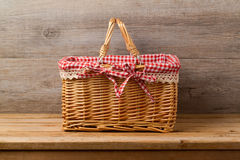 Picnic basket with checked cloth on table Royalty Free Stock Images