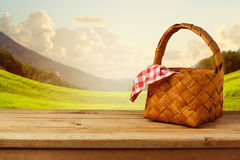 Picnic basket with checked tablecloth on wooden table Stock Photography