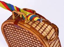Picnic basket with a colorful umbrella. Wicker basket with a colorful umbrella attached together Stock Photo
