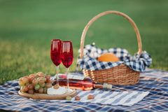 Picnic basket with drinks, food and fruit on green grass outside in summer park royalty free stock images