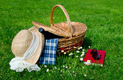 Picnic basket in the field. Summer picnic with hat, book and wine in a field Stock Images