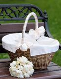 Picnic basket and flowers bouquet. On wooden bench Royalty Free Stock Images