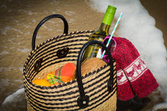 Picnic basket in a foam of sea water. Stock Photos