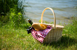 Picnic basket with food. And cider bottle near the water Stock Photo