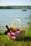 Picnic basket with food. And cider bottle near the water Royalty Free Stock Photo