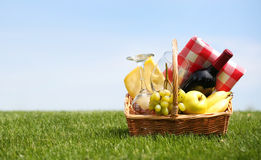 Picnic basket with food on green grass Royalty Free Stock Photos