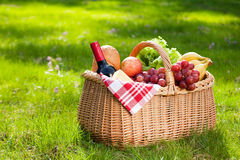 Picnic basket with food on green grass.