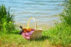 Picnic basket with food near the water Royalty Free Stock Photography