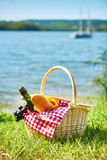Picnic basket with food near the water Stock Photography