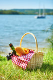 Picnic basket with food near the water. Picnic basket with food and cider bottle near the water Stock Photos