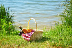 Picnic basket with food near the water. Picnic basket with food and cider bottle near the water Royalty Free Stock Images