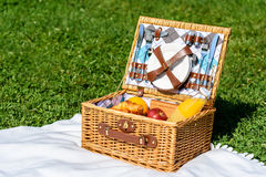 Picnic Basket Food On White Blanket. In Summer Stock Photos