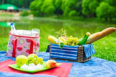 Picnic basket with fruits, bread and bottle of Stock Image