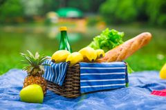 Picnic basket with fruits, bread and bottle of Stock Photos