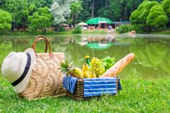 Picnic basket with fruits, bread and hat on straw Stock Photo
