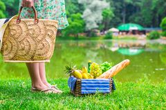 Picnic basket with fruits, bread and hat on straw Stock Image