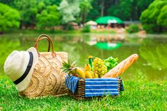 Picnic basket with fruits, bread and hat on straw Stock Images