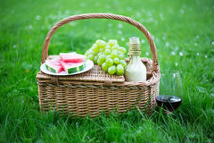 Picnic basket with fruits and glass of wine on green grass in pa Royalty Free Stock Photography