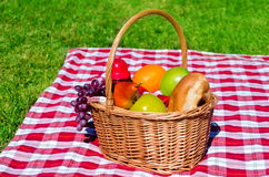 Picnic basket with fruits. On the grass background Royalty Free Stock Photos