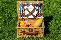 Picnic Basket With Fruits, Juice And Croissants. Picnic Basket With Orange Juice Bottle, Apples, Peaches, Oranges And Croissants On Green Grass In Spring stock photos