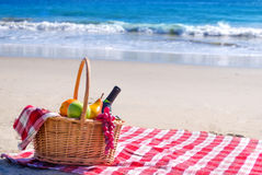 Picnic basket with fruits by the ocean. Picnic background with basket and fruits by the ocean Stock Photo
