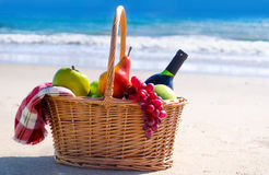 Picnic basket with fruits by the ocean Stock Photos