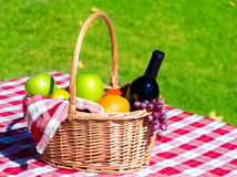 Picnic basket with fruits and wine. On grass background Stock Photo
