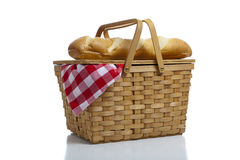 Picnic Basket with Gingham. A wicker picnic basket with a red gingham cloth and bread on a white background Royalty Free Stock Photography