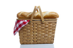 Picnic Basket with Gingham. A wicker picnic basket with a red gingham cloth and bread on a white background Stock Photo