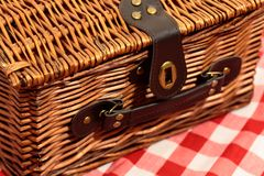 Picnic basket on a gingham background. With handle and strap Royalty Free Stock Images