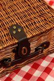 Picnic basket on a gingham background. With handle and strap Royalty Free Stock Photos