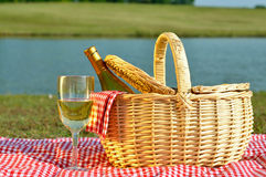 Picnic Basket and Glass of Wine. Bottle of white wine in picnic basket with glass of wine beside it.  Red gingham blanket and napkin with lake in background Stock Photo