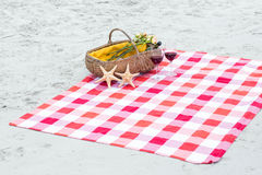 Picnic basket with glasses of red wine and starfishes on a blanket