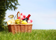Picnic basket on green field Stock Photos