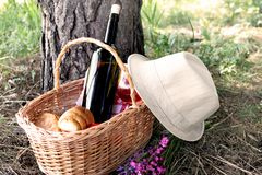 Picnic basket with a hat placed near. Picnic basket with wine, croissants,field flowers and a hat placed near Royalty Free Stock Image
