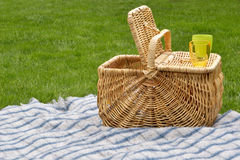Picnic basket open. Picnic basket on blanket in grass field Stock Images