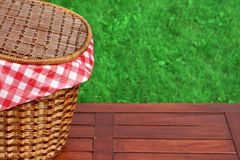 Picnic Basket On The Outdoor Rustic Wood Table Close-up. Picnic Basket On The Outdoor Rustic Wood Table Closeup, Bright Summer Green Grass In The Background Stock Photos