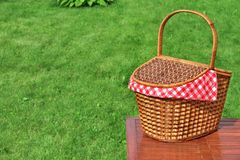 Picnic Basket On The Outdoor Rustic Wood Table Close-up. Picnic Basket On The Outdoor Rustic Wood Table Closeup, Bright Summer Green Grass In The Background Royalty Free Stock Photo