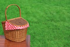 Picnic Basket On The Outdoor Rustic Wood Table Close-up. Picnic Basket On The Outdoor Rustic Wood Table Closeup, Bright Summer Green Grass In The Background Royalty Free Stock Images