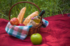 Picnic basket on the red blanket at nature. Apples, white wine a Stock Photo