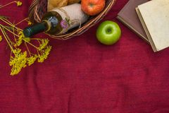 Picnic basket on the red blanket top view. Apples, white wine, b. Ooks, baguettes and yellow wild flowers Royalty Free Stock Image