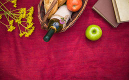 Picnic basket on the red blanket top view. Apples, white wine, b. Ooks, baguettes and yellow wild flowers Stock Image