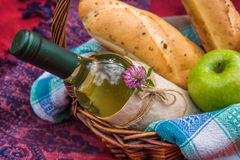 Picnic basket on the red blanket top view. Apples, white wine an Stock Photo