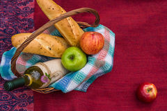 Picnic basket on the red blanket top view. Apples, white wine an Royalty Free Stock Photo